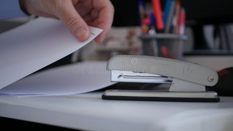 Zakenman Putting Contracts Pages die samen een Bureau Metaalhulpmiddel met behulp van stock foto