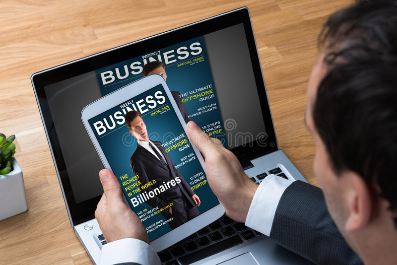 Zakenman Reading Business Magazine op Tablet stock fotografie