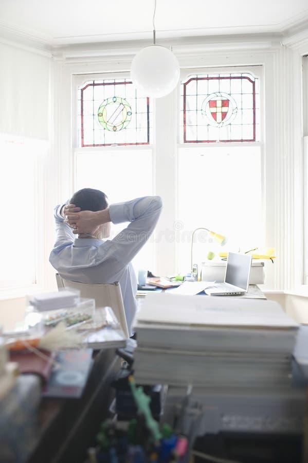 Zakenman Relaxing At Desk in Huisbureau royalty-vrije stock afbeeldingen