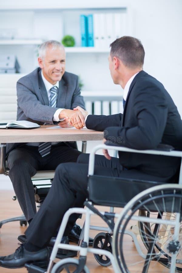 Zakenman in rolstoel het schudden handen met collega royalty-vrije stock afbeelding