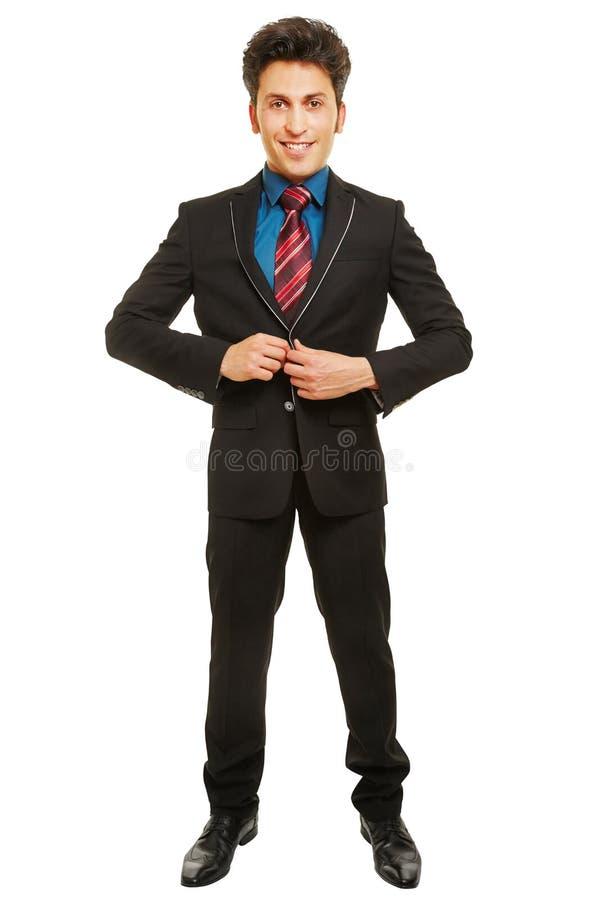 Zakenman sluitende knoop van zijn jasje royalty-vrije stock afbeelding