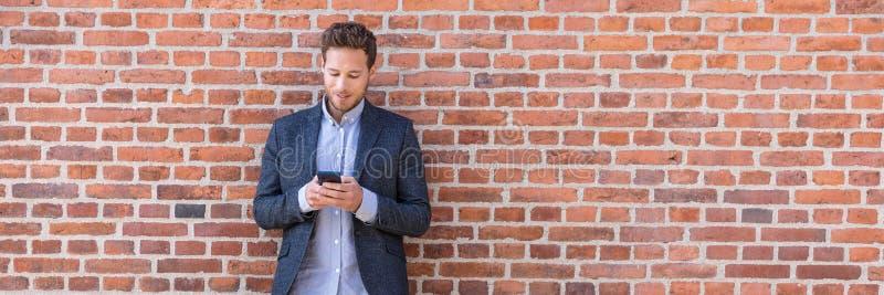 Zakenman sms texting telefoon app in stadsstraat op bakstenen muurachtergrond Smartphone van de bedrijfsmensenholding in slimme v stock afbeeldingen