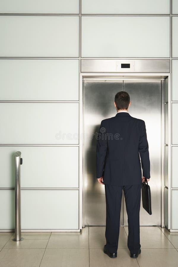 Zakenman Standing In Front View Elevator stock foto's