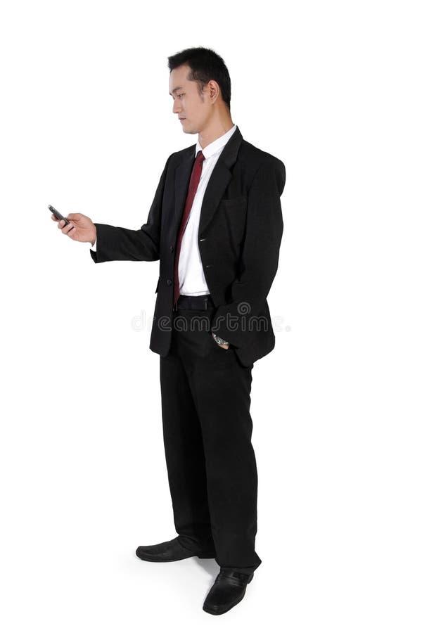 Zakenman status, die op telefoon controleren stock foto