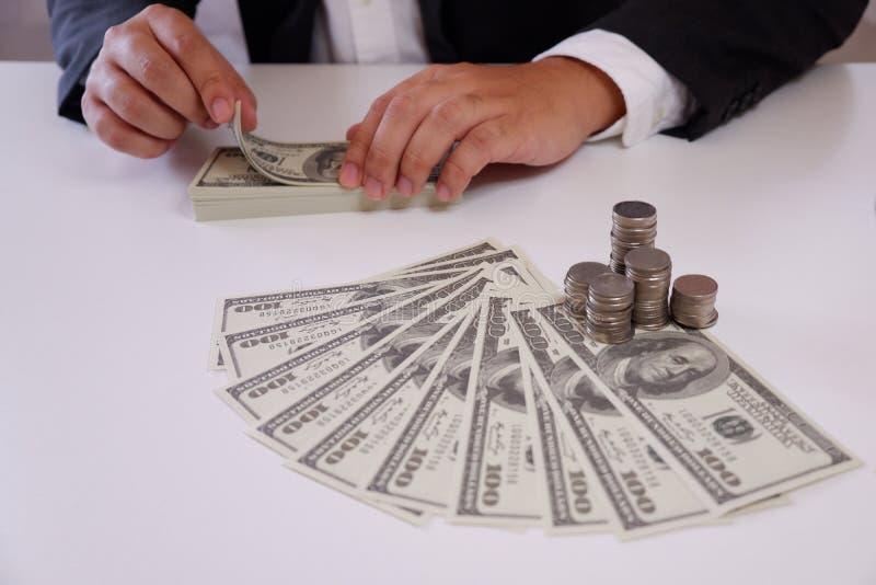 Zakenman tellend geld met muntstukken en geld over het bureau stock fotografie