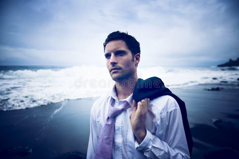 Zakenman Thinking door het Strand met Ernstig Gezicht stock foto