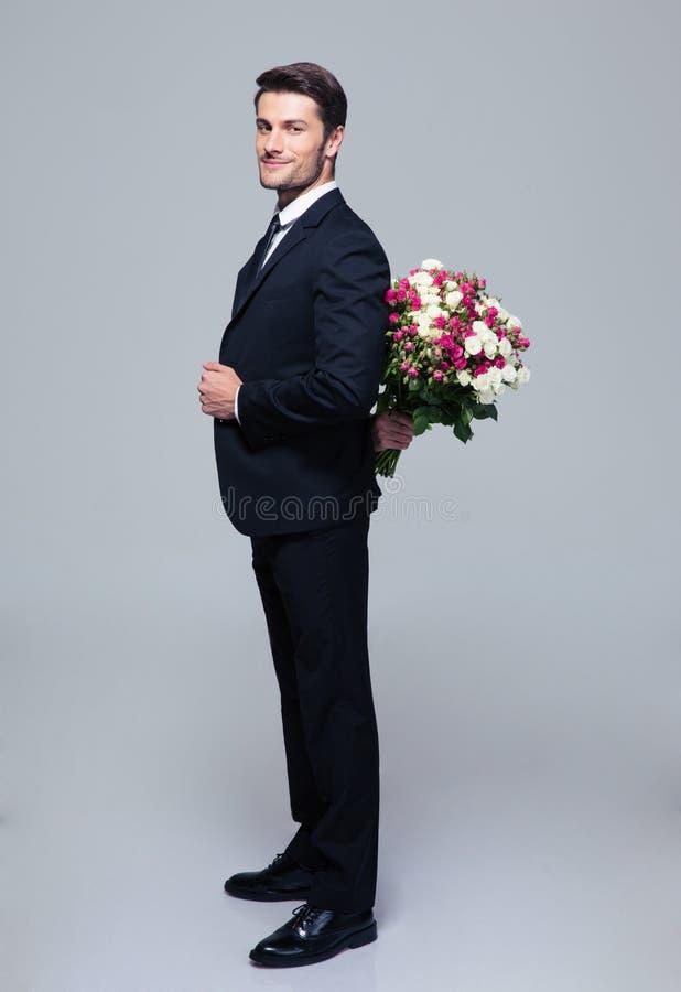 Zakenman verbergend boeket van bloemen achter zijn rug royalty-vrije stock afbeeldingen