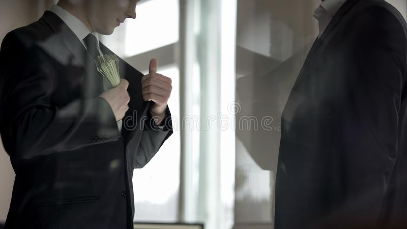 Zakenman verbergend geld in kostuumjasje, twee partners die bedrijfswinst delen royalty-vrije stock afbeelding