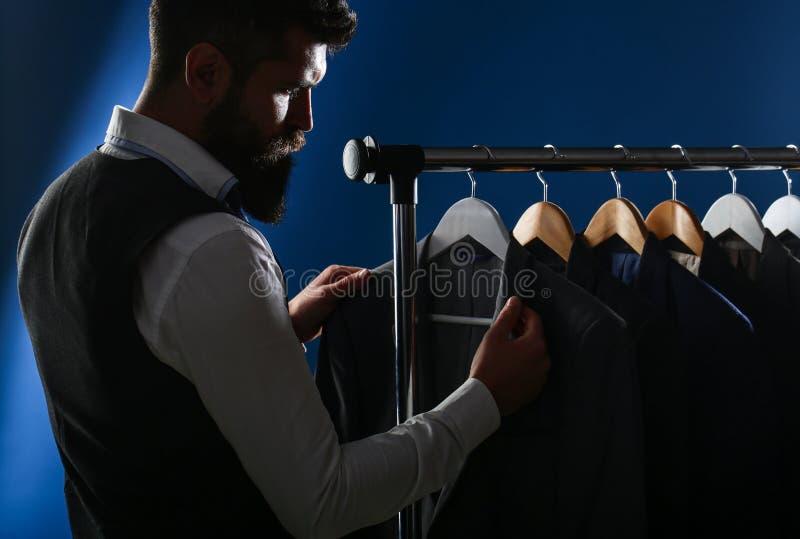Zakenman in vest, rij van kostuums in winkel Modieuze mens in een doekjasje Het is in de toonzaal, die op kleren proberen stock foto