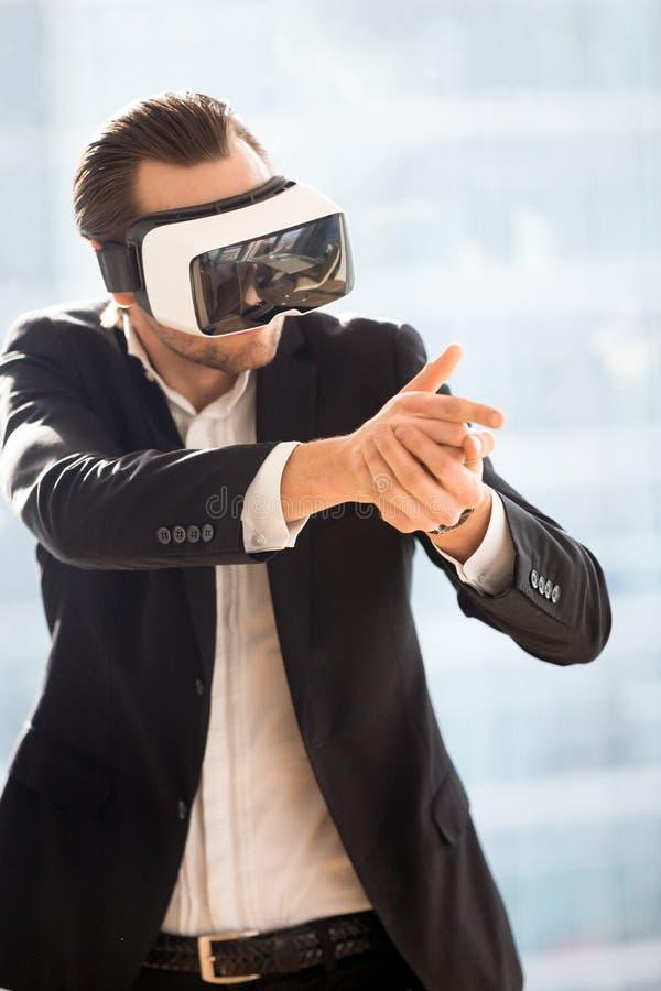 Zakenman in VR-hoofdtelefoon met speel de schutterspel van het vingerkanon stock foto's
