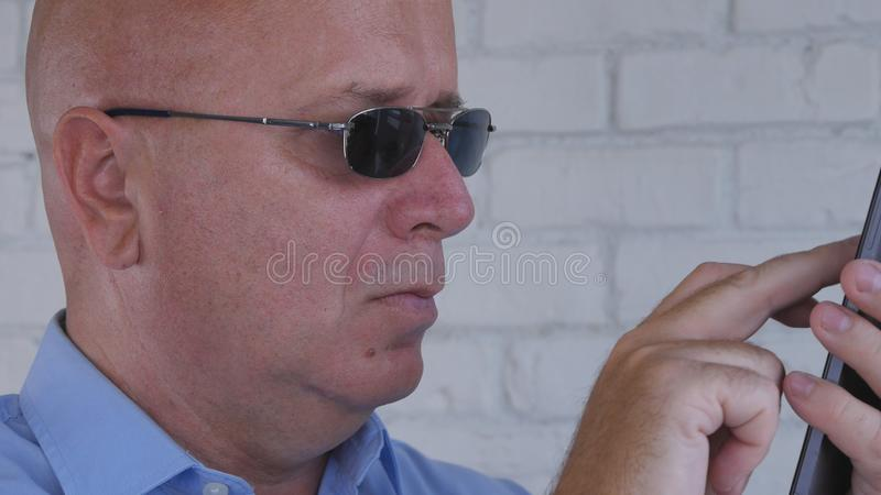 Zakenman Wearing Sunglasses Text die Smartphone-Mededeling gebruiken royalty-vrije stock foto's
