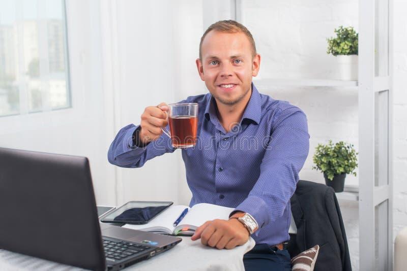 Zakenman werken in bureau, zittend bij een lijstholding vormt en kijkend recht tot een kom royalty-vrije stock foto