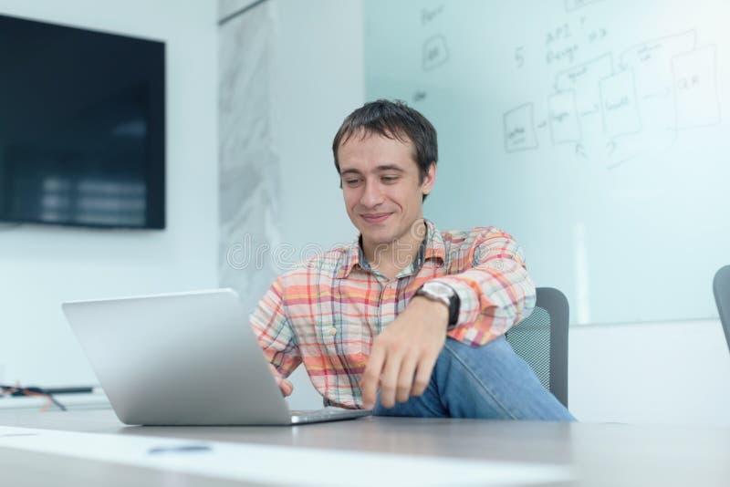 Zakenman werkend laptop zittingsbureau stock afbeelding