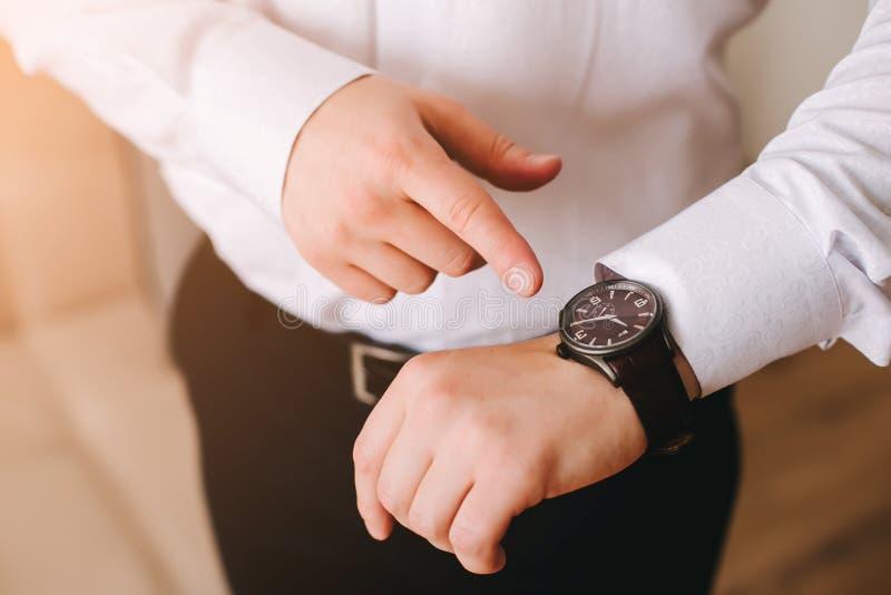 Zakenman in wit overhemd die zijn Zwitsers polshorloge op zijn hand bekijken en op de tijd letten royalty-vrije stock foto
