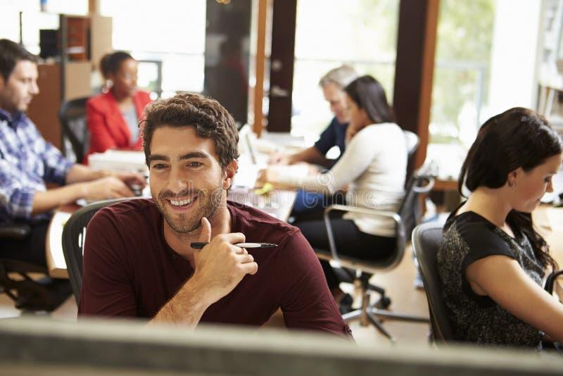 Zakenman Working At Desk met Vergadering op Achtergrond royalty-vrije stock afbeeldingen