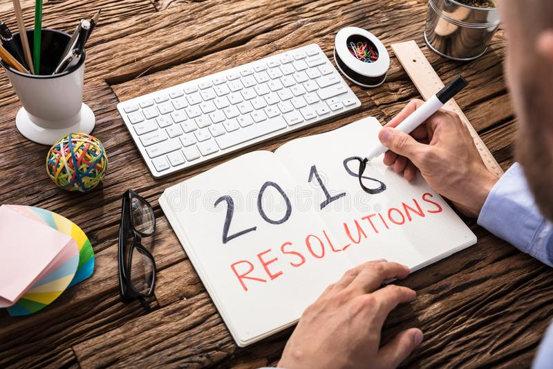 Zakenman Writing 2018 Resoluties over Notitieboekje royalty-vrije stock afbeelding