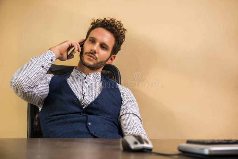 Zakenman in zijn bureau die op celtelefoon spreken royalty-vrije stock afbeelding