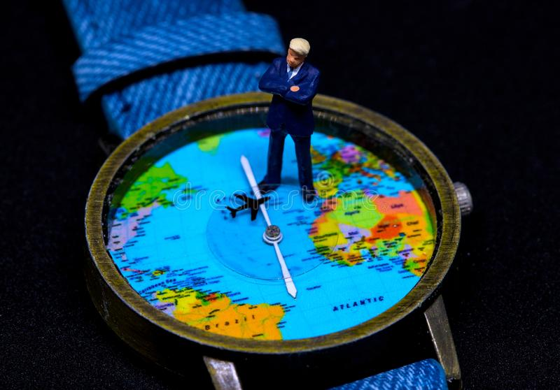 Zakenmanbeeldje op globaal kaarthorloge Bedrijfsconcept wereldwijd royalty-vrije stock foto's