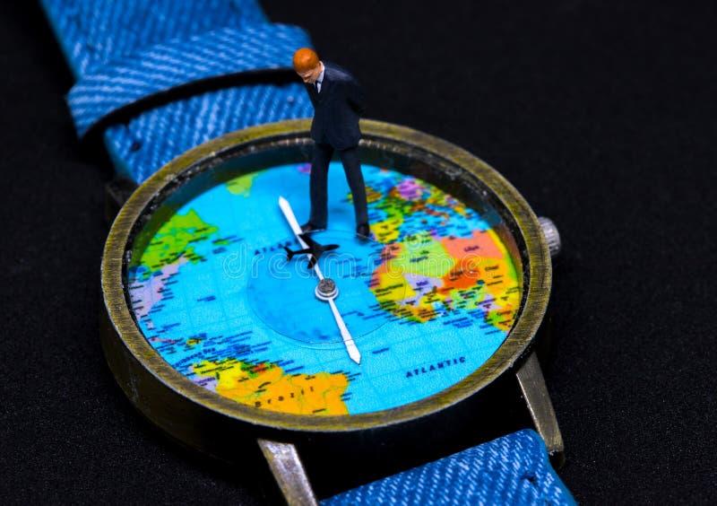 Zakenmanbeeldje op horloge De klok van de wereldkaart Bedrijfsconcept wereldwijd stock fotografie