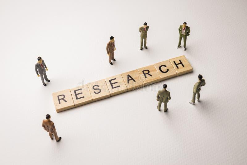 Zakenmancijfers die bij conceptuele het onderzoek samenkomen stock afbeelding