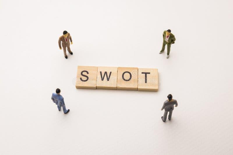 Zakenmancijfers die op conceptueel SWOT samenkomen stock foto