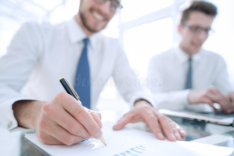 Zakenmancontrole over kosten en het doen van het rapport van de financiëngrafiek op kantoor stock afbeeldingen