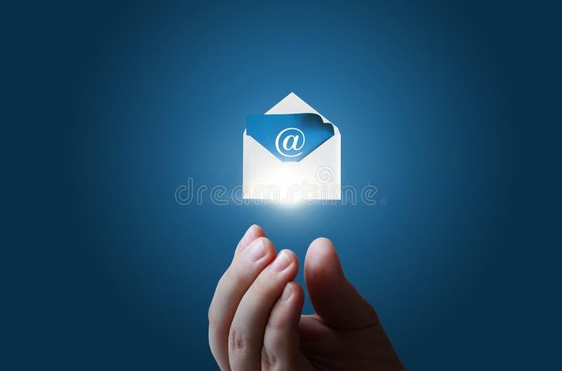 In zakenmanhand de envelop met het elektronische bericht stock foto
