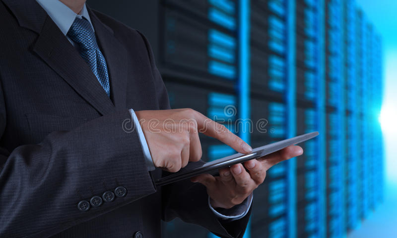 Zakenmanhand die tabletcomputer en serverruimte gebruiken stock foto