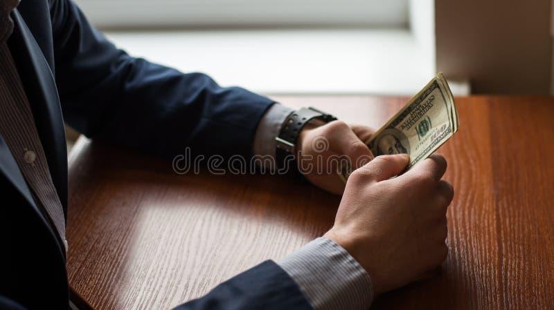 Zakenmanhand het grijpen geld, de rekeningen van Amerikaanse dollarusd Mens in kostuum Houten achtergrond royalty-vrije stock afbeelding