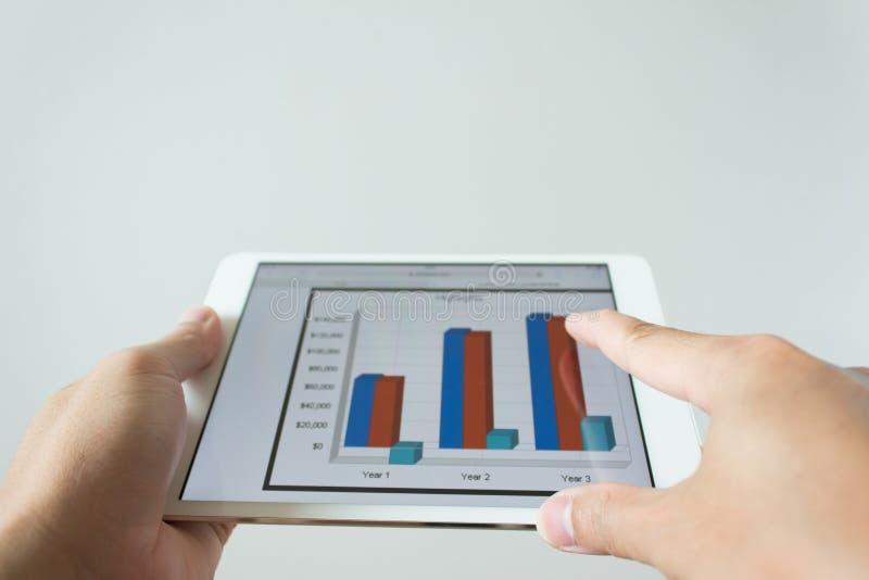 Zakenmanhand wat betreft het scherm van tabletcomputer met markt royalty-vrije stock afbeelding