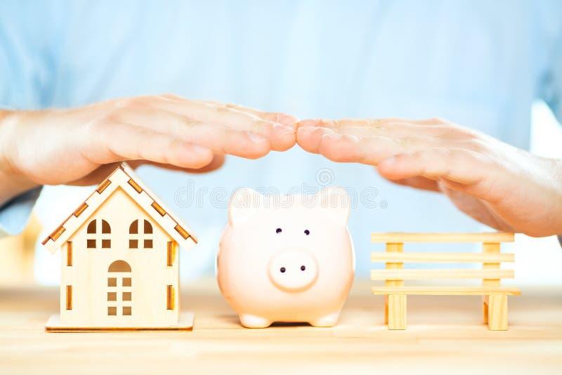 Zakenmanhanden boven een spaarvarken, huismodel en een bank Hypotheekplan, verzekering en de woonstrategie van de belastingsbespa royalty-vrije stock fotografie