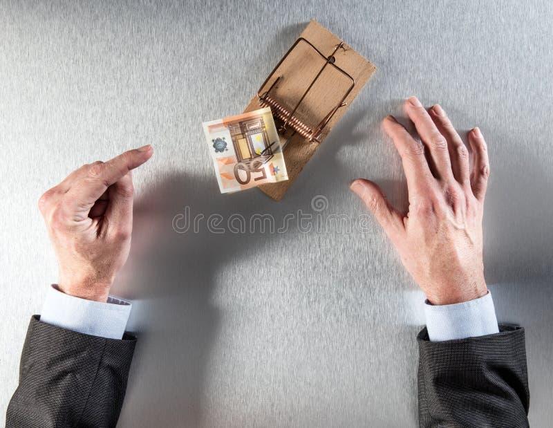 Zakenmanhanden die aarzeling tonen die euro geld in muisval onder ogen zien stock foto's