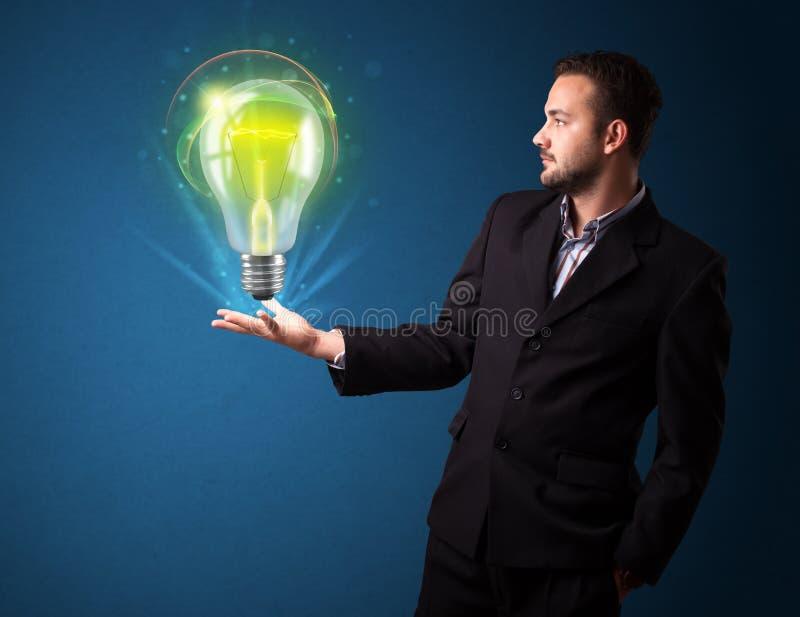 Zakenmanholding die lightbulb in zijn hand gloeien stock fotografie