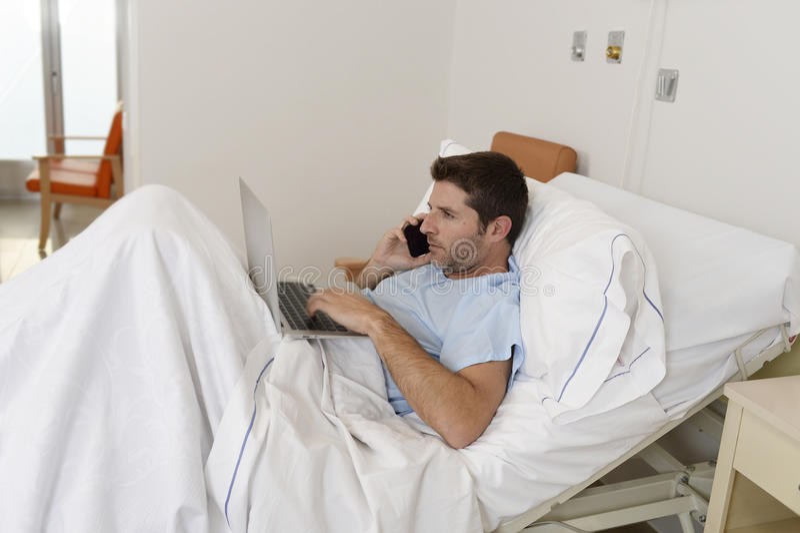 Zakenmanintern als patiënt in het ziekenhuis die aan ziekte die en werken lijden gelukkig en bij kliniekbed wordt ontspannen royalty-vrije stock foto