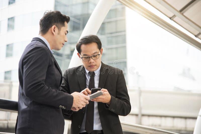 Zakenmanpartner die met mobiele telefoon bespreken royalty-vrije stock foto