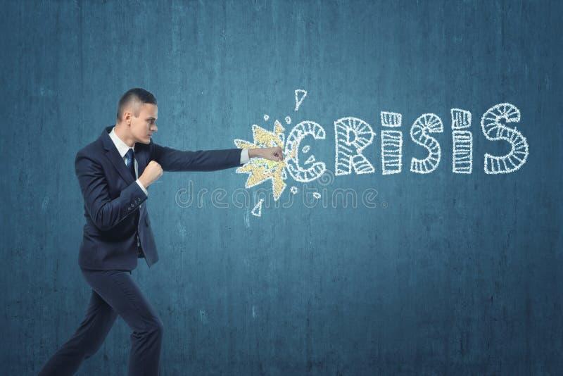 Zakenmanponsen hard de woord` crisis ` op donkerblauwe muur wordt geschreven die stock foto's
