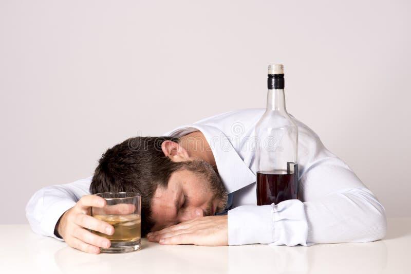 Zakenmanslaap van whisky bij bureau op duidelijke achtergrond wordt gedronken die royalty-vrije stock foto