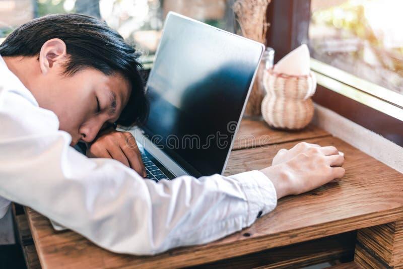 Zakenmanslaap Zijaanzicht van de jonge mens in overhemd en bandslaap terwijl het zitten op zijn werkende plaats stock fotografie
