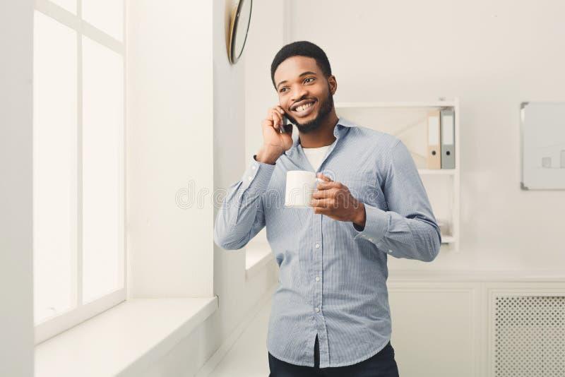 Zakenmantelefoon die op telefoon dichtbij venster spreken royalty-vrije stock foto