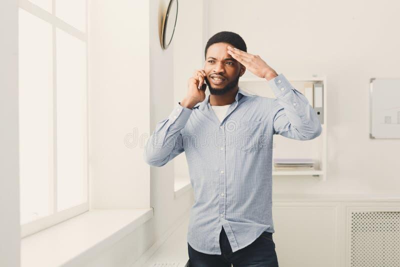 Zakenmantelefoon die op telefoon dichtbij venster spreken royalty-vrije stock afbeelding
