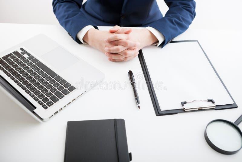 Zakenmanzitting alleen en samen gevouwen zijn handen stock afbeelding