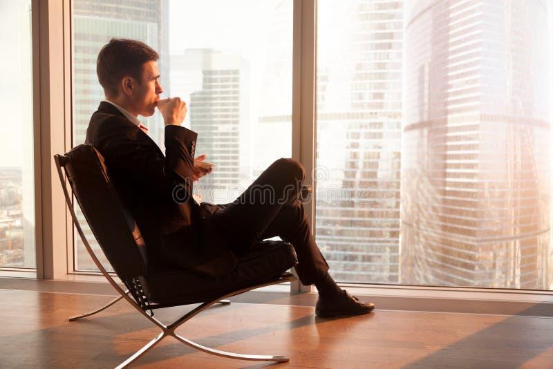Zakenmanzitting als bureauvoorzitter die van koffie in morni genieten stock afbeelding