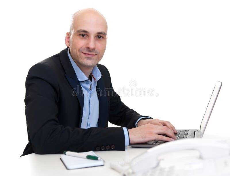 Zakenmanzitting bij bureau, die aan laptop computer werken stock afbeeldingen