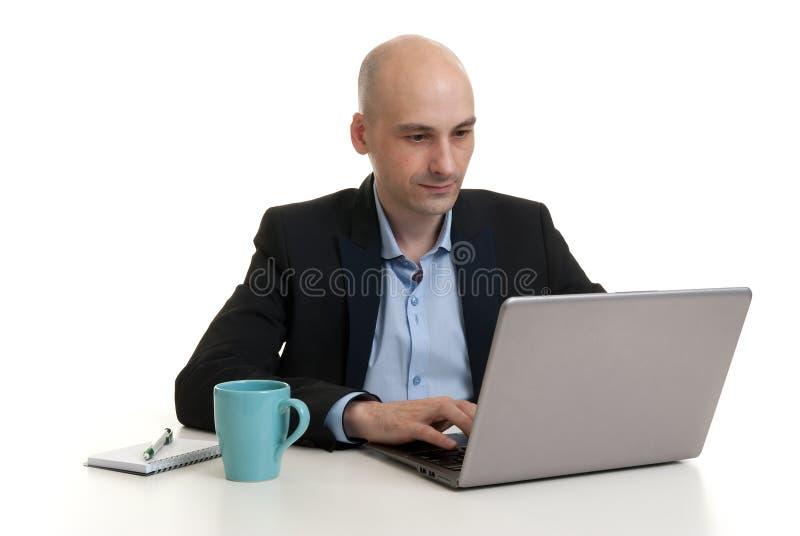 Zakenmanzitting bij bureau, die aan laptop computer werken stock foto