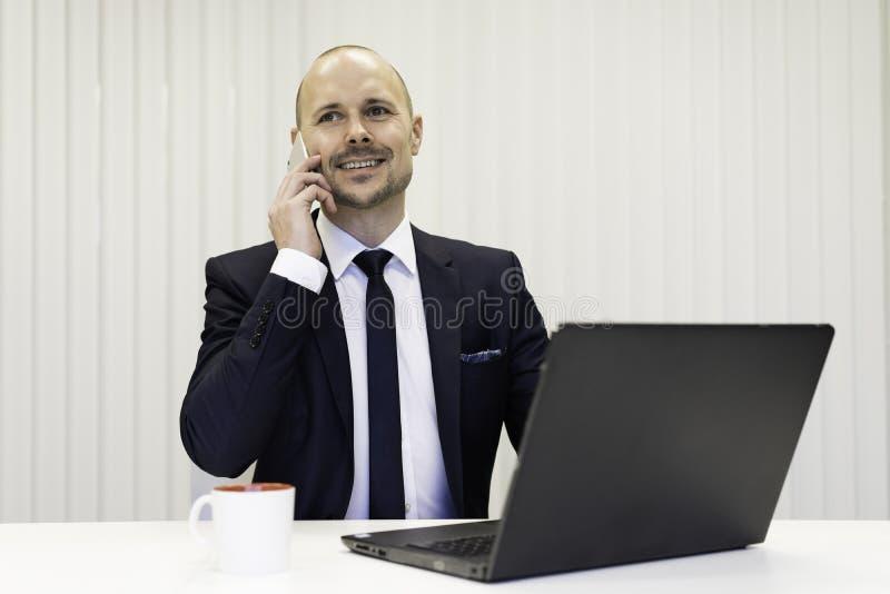 Zakenmanzitting bij bureau die in mobiele telefoon spreken royalty-vrije stock afbeeldingen