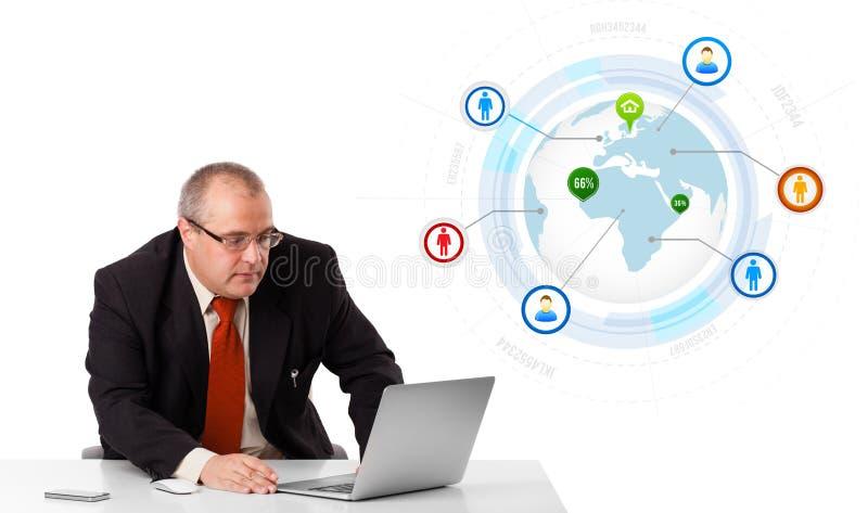 Zakenmanzitting bij bureau en het kijken laptop met bol en zo royalty-vrije stock foto's