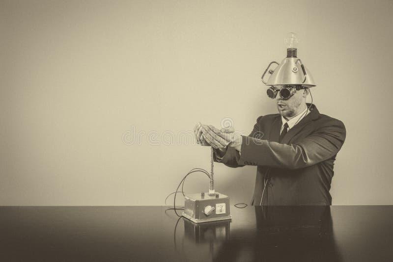 Zakenmanzitting bij bureau met machine stock afbeeldingen