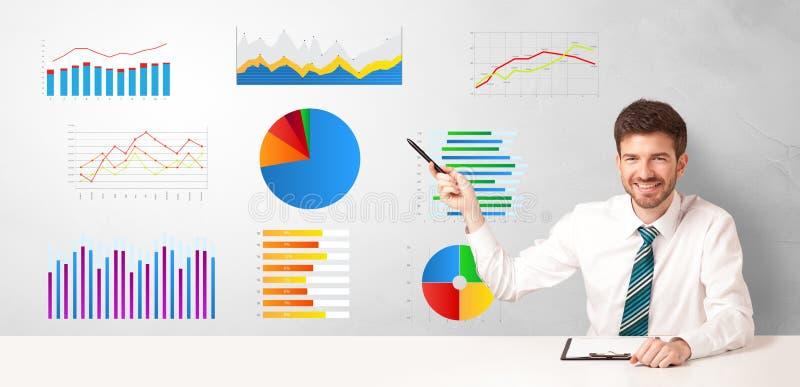 Zakenmanzitting bij bureau met rapporten en grafieken royalty-vrije stock afbeeldingen
