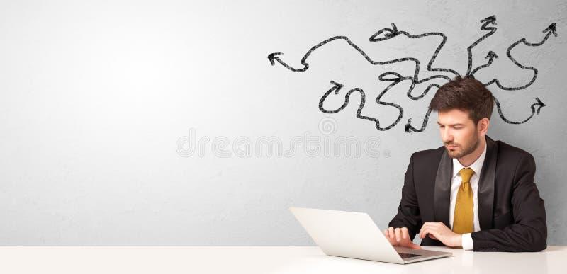 Zakenmanzitting bij bureau met rond pijlen stock fotografie