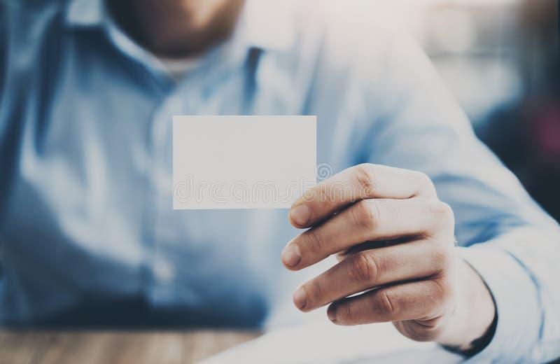 Zakenmanzitting bij de houten lijst en het tonen van een leeg adreskaartje horizontaal Model royalty-vrije stock foto's